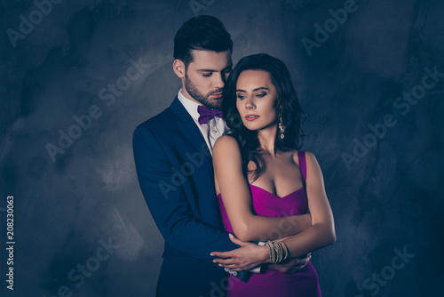 Fototapeta Portrait of pretty charming mrs in purple dress with jewelry half face mr in tuxedo bowtie holding hand in pocket of pants embracing his lover lovely attractive couple isolated on grey background obraz na płótnie