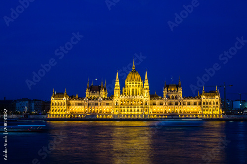 Fotografia  Illuminated Budapest parliament building at night with dark sky and reflection i