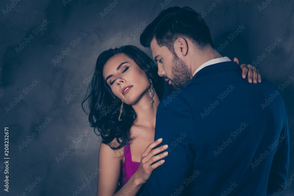 Fototapeta Portrait of pretty charming mrs in purple dress with jewelry half face mr in tuxedo bowtie holding hand in pocket of pants embracing his lover lovely attractive couple isolated on grey background - obraz na płótnie