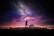 canvas print picture - Night time long exposure landscape photography. A man standing in a high place reaching up in wonder to the Milky Way galaxy, photo composite.