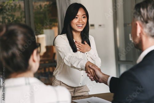 Photo  Business, career and placement concept - two business partners in office shaking