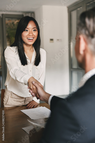 Fotografía  Business, career and placement concept - happy asian woman handshaking with male