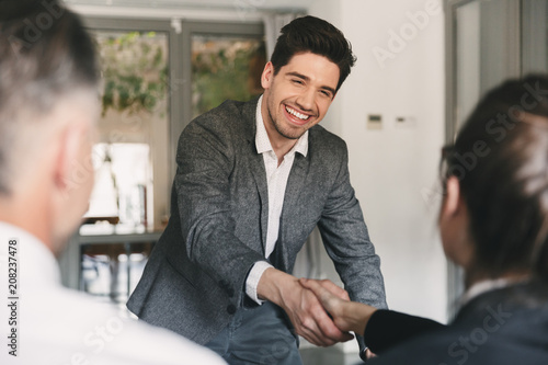 Fototapeta Business, career and placement concept - happy european man wearing suit rejoicing and shaking hands with group of employee, when was recruited during interview in office obraz