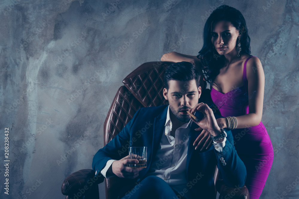 Fototapeta Portrait of brutal gentleman in formal wear sitting in leather chair holding glass with whiskey cigar in hands, charming pretty lady standing near looking at camera isolated on grey background