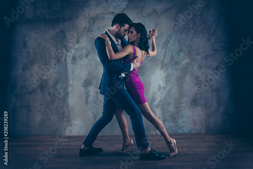 plakat Full size body portrait of lovely attractive couple standing close in tango position face to face dancing, charming lady in purple tight dress gentlemen in tux isolated on grey background movement