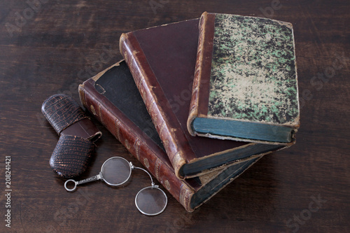 old books piled on an antique wooden furniture