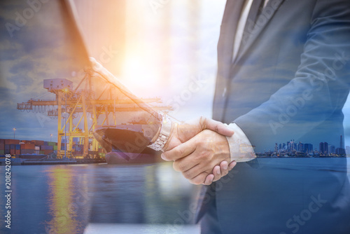 Fotografia, Obraz  Logistic partner, Two businessmen shaking hand with Industrial port loading cont