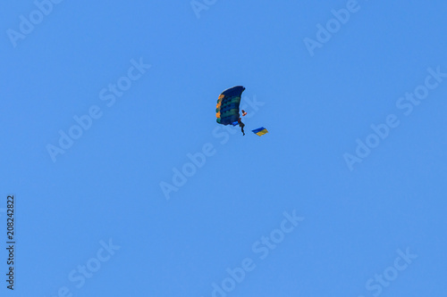 Papiers peints Aerien Parachutist carrying flag of Ukraine in blue clear sky