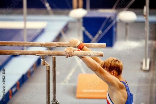 Foto auf Leinwand Gymnastik men gymnast exercises on parallel bars in gymnastics