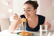canvas print picture - Young woman eating tasty pasta in cafe
