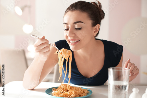 Foto op Canvas Kruidenierswinkel Young woman eating tasty pasta in cafe