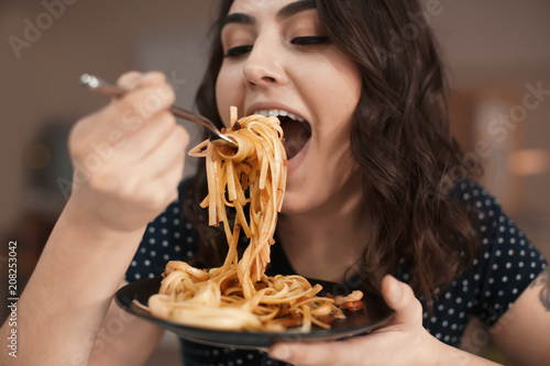 Fotomural Young woman eating tasty pasta in cafe