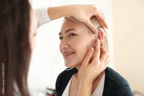 Fotografía  Otolaryngologist putting hearing aid in woman's ear on light background