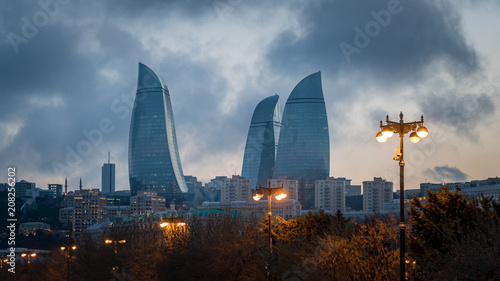 Fotomural  Baku evening cityscape with flaming towers and reflections in the Caspian sea ba