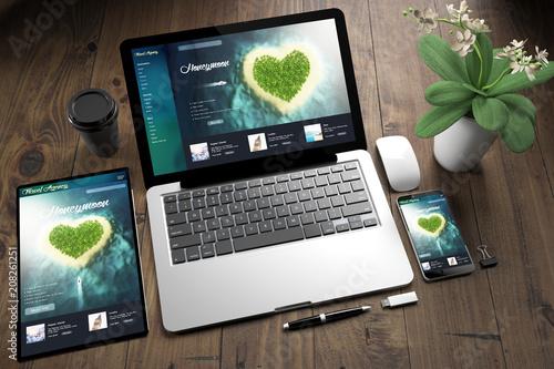 Fotografia  tablet, laptop and mobile phone over wooden desktop showing honeymoon website