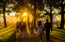 At Sunset, People Spend The Weekend With The Whole Family In The City Garden.Summer Family Weekend.