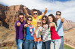 travel, tourism and people concept - group of happy friends pointing at you over grand canyon national park background