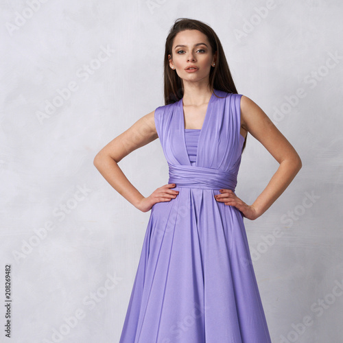 16523fa480 Beautiful long haired young woman dressed in stylish purple bandeau maxi  dress posing against white wall on background. Elegant brunette female  model ...