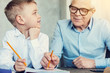 canvas print picture - Doing exercises. Caring clever attentive grandfather helping his cute little pupil to do the homework