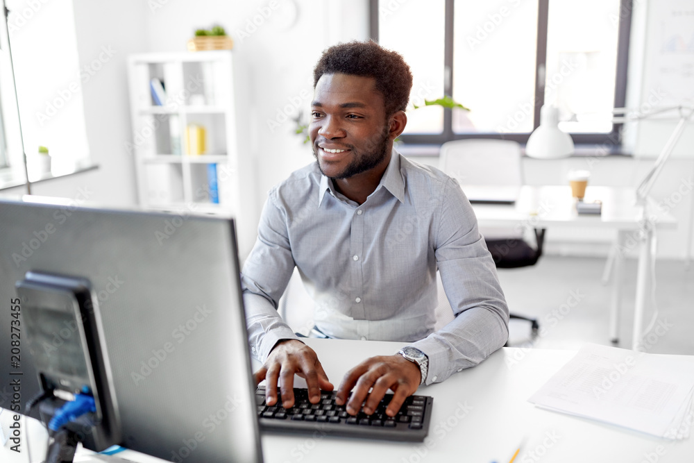 Fototapeta business, people and technology concept - african american businessman with computer working at office