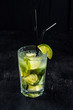 Cocktail mojito with lime and ice on black background