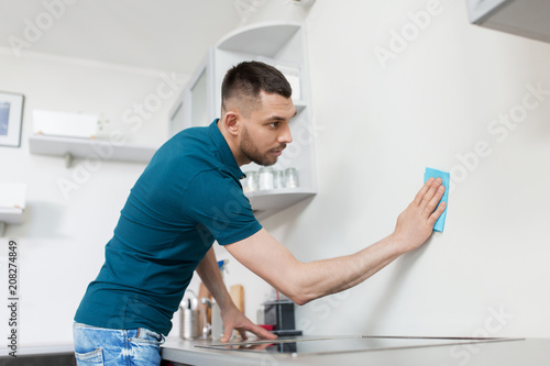 Fototapety, obrazy: household and people concept - man with cloth cleaning wall at home kitchen