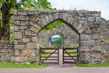 Torlundy, Scotland - June 11, 2012: Natural Stone Gate With Triangular Bow To The Domain Of Inverlochy Castle Near Fort William. Green Grass And Tree Foliage. Gray Sky.