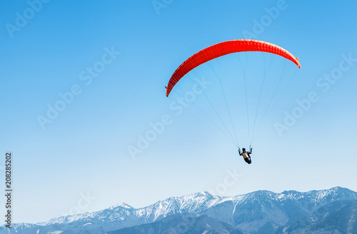 Poster de jardin Aerien Sportsman on red paraglider soaring over the snowy mountain peaks