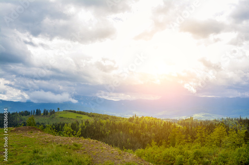 Staande foto Bleke violet A beautiful mountain landscape - mountains, clouds, clouds, trees, and rays of the sun.
