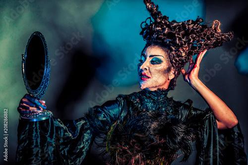 Valokuva gruselige Hexe mit Handspiegel