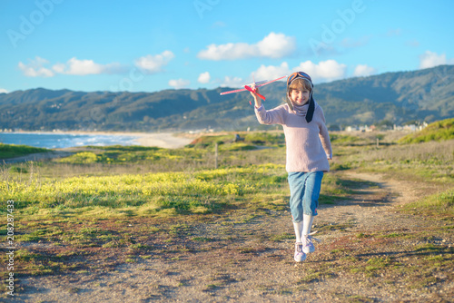 21b93044667 Girl in aviator hat playing pilot with toy plane outside - Buy this ...