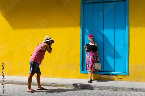 obraz PCV Man taking a photo of a girl against a yellow wall