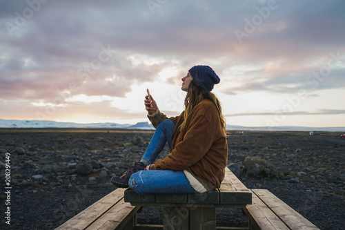 Person sitting on table and looking up with smartphone