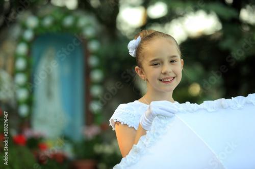 Śliczna mała dziewczynka w białej sukience na tle kapliczce. - fototapety na wymiar