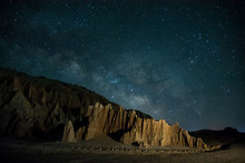 Milky Way And Late Night Stars Raising Over Rugged Desert Landscape