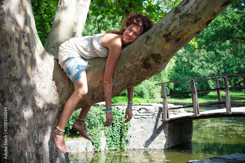Valokuva  funny smiling young woman relaxing on tree in park summer day