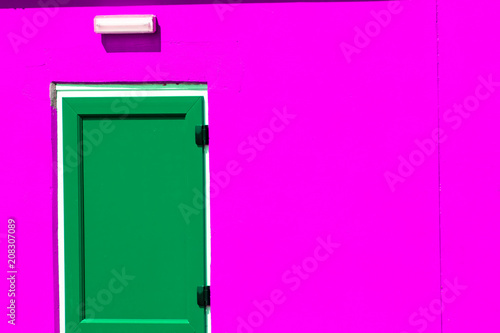 Fotografía  Vibrant colorful paint. Green painted door on neon pink building.