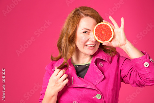 Beautiful adult woman holding one half of juicy grapefruit covering her eye Poster