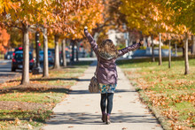 One Young Happy Woman, Arms Raised On Sidewalk Street Walking In Washington DC, USA In Alley Of Golden Orange Yellow Foliage Autumn Fall Trees