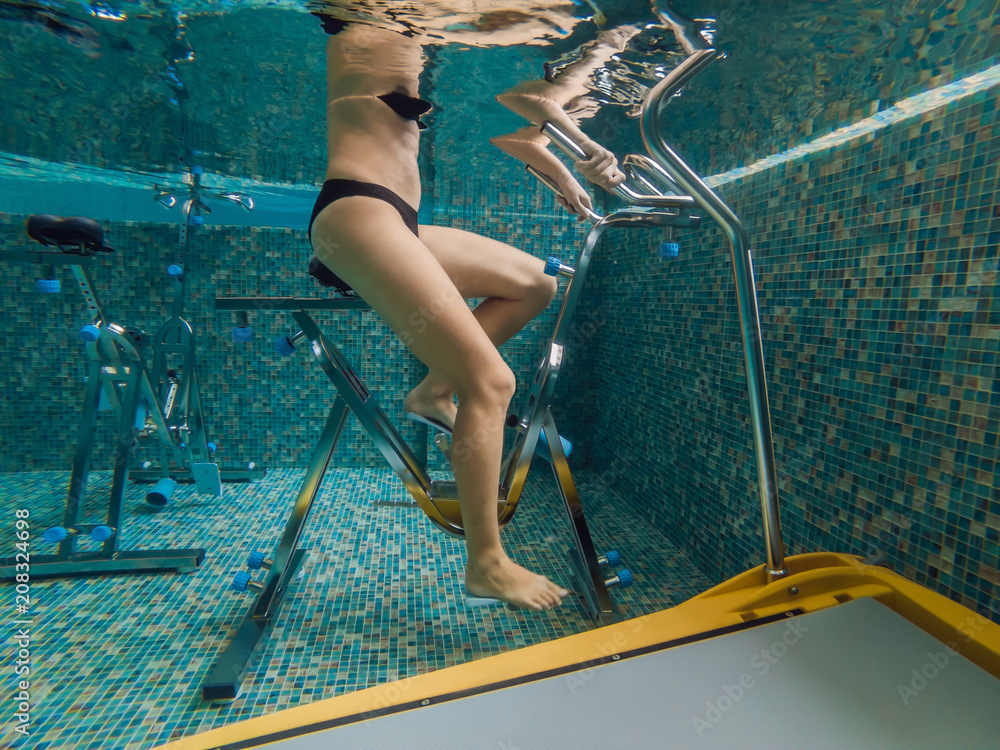 Fototapeta Young woman on bicycle simulator underwater in the pool