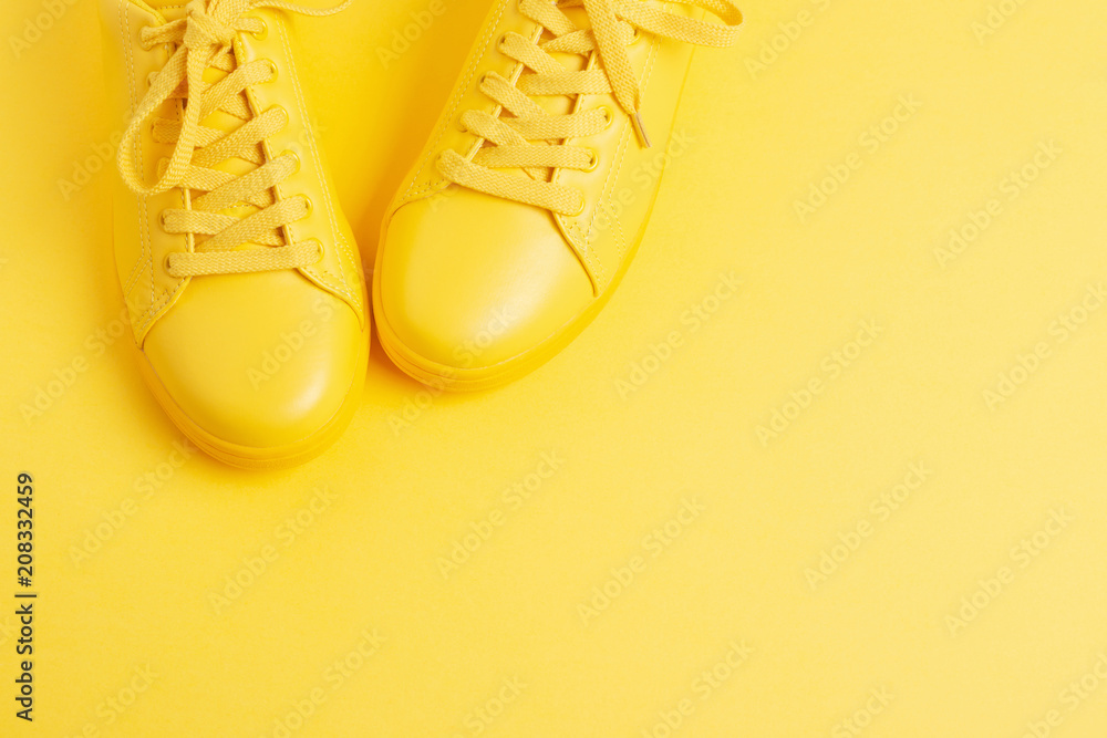 Fototapeta Pair of yellow shoes on yellow background. Trendy summer color, monochrome image. Hipster concept. Shot at angle.