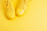 Pair of yellow shoes on yellow background. Trendy summer color, monochrome image. Hipster concept. Shot at angle. - 208332459