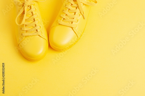 Fotografia  Pair of yellow shoes on yellow background