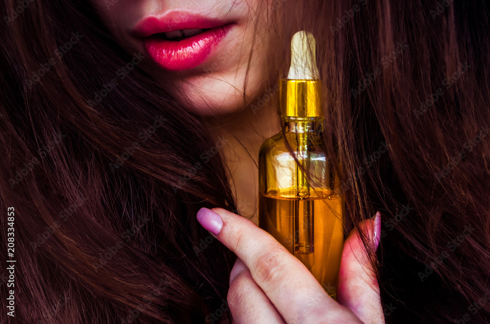 Fototapety, obrazy:  a woman with beautiful hair holds hair oil. The concept of hair care