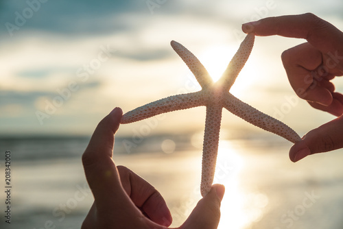 Soft focus on woman hand holding starfish over sea and Sandy beach in background during sunset for summer holiday and vacation concept Wallpaper Mural