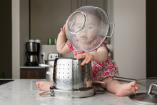 Funny Baby With Colander On Head Playing With Kitchenware