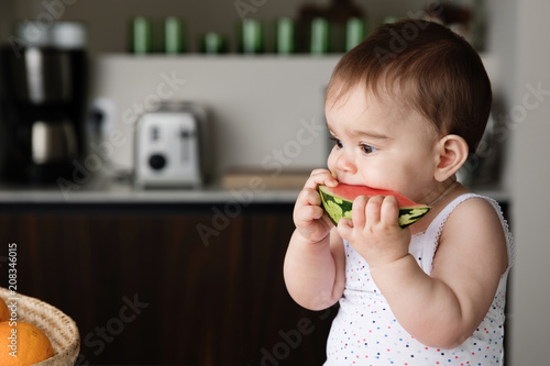 Baby eating a slice of watermelon in kitchen