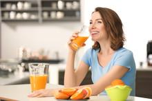 Beautiful Woman Drinking Citrus Juice In Kitchen