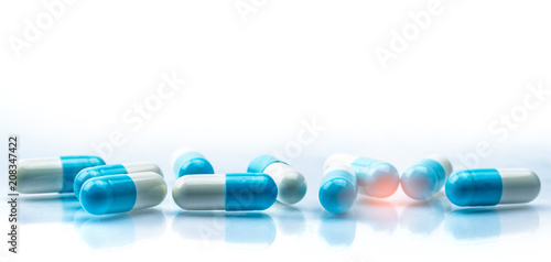 Slika na platnu Blue and white capsules pill spread on white background with shadow and copy space