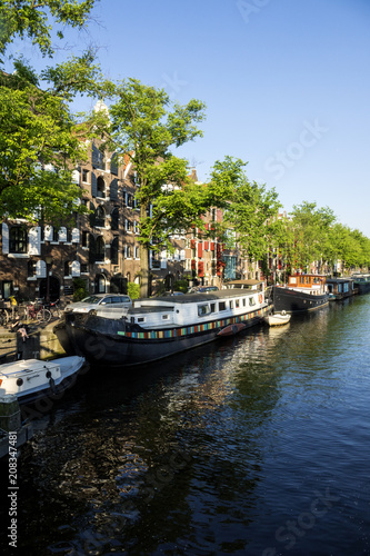 Foto op Canvas Amsterdam On the banks of the canals of Amsterdam, magnificent boats are transformed into houses